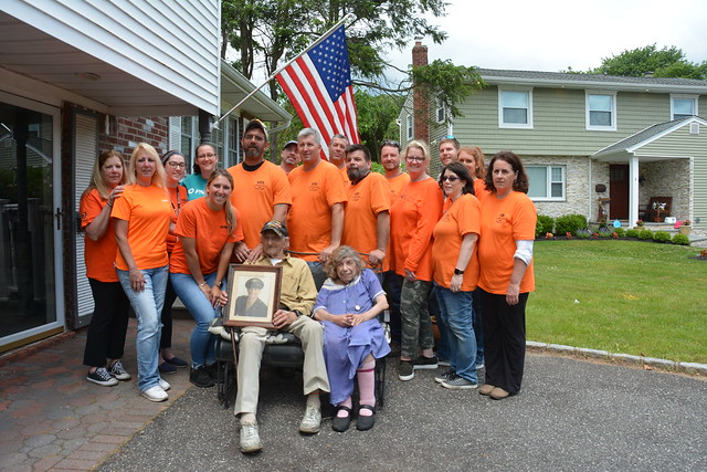 PSEG Long Island employees pose with 96-year-old World War II Army Air Corps veteran Morris Koffer, and his wife, Edith. The group volunteered for the day cleaning up inside and outside the Koffers' home on the 75th anniversary of D-Day.