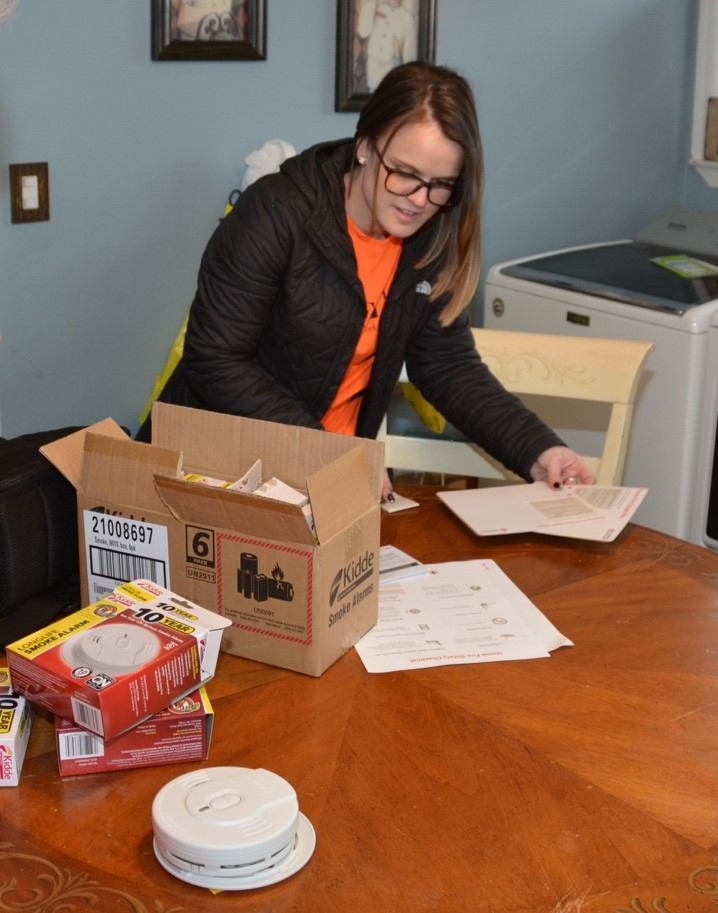 "PSEG Long Island's Brittany Venturo of Smithtown assembles smoke alarms in a New Hyde Park home—doing her part to keep local families safe by participating in the American Red Cross ""Sound the Alarm"" campaign."