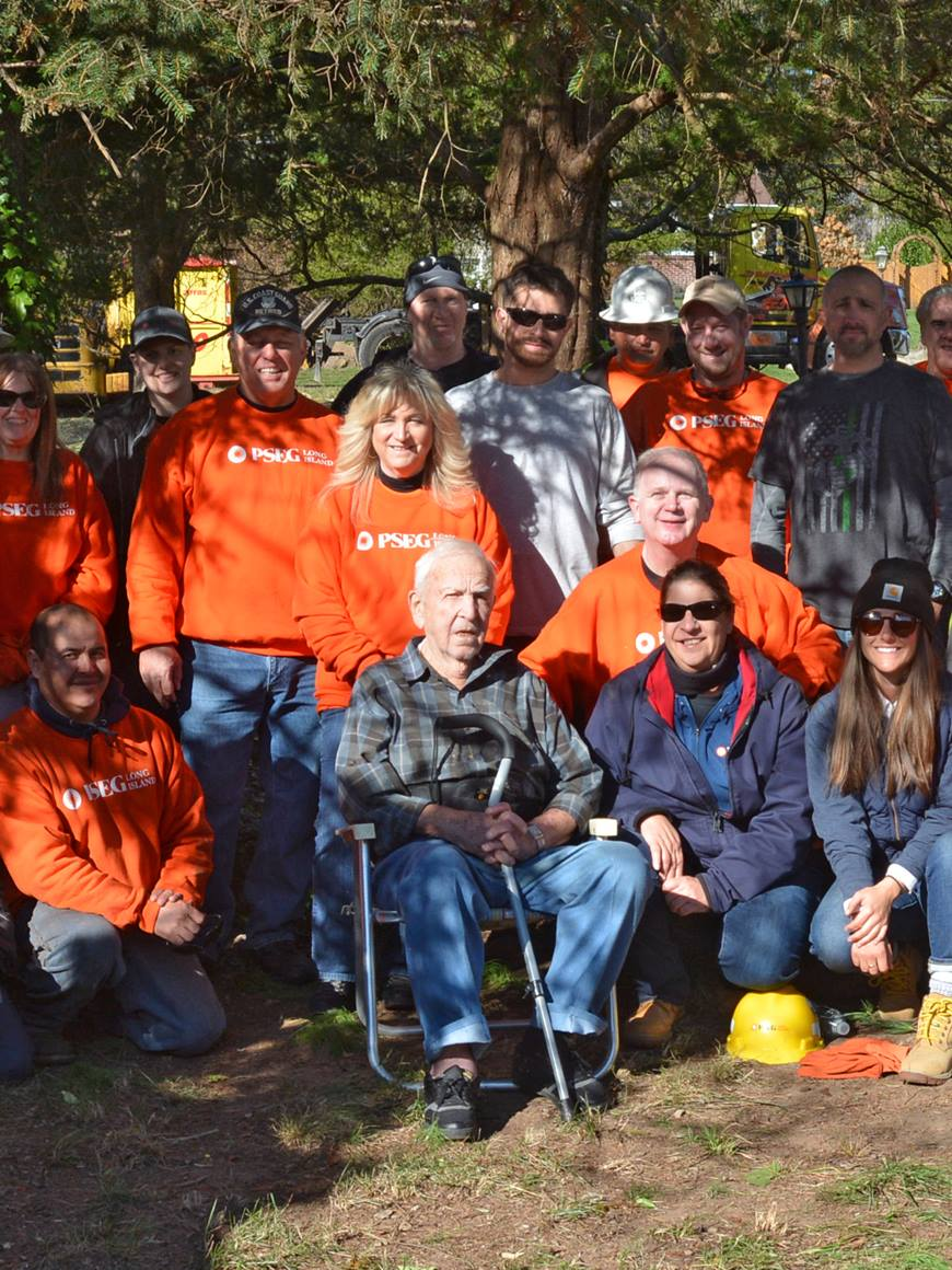 World War II veteran and retired teacher Clem Novak got a visit and a yard cleanup from more than 20 PSEG Long Island employees, including Coast Guard veteran Bart Polizzotti (left, in orange shirt and gray cap), of Sound Beach, and Navy veteran Kevin Rodgers (right, crouching), of Huntington.