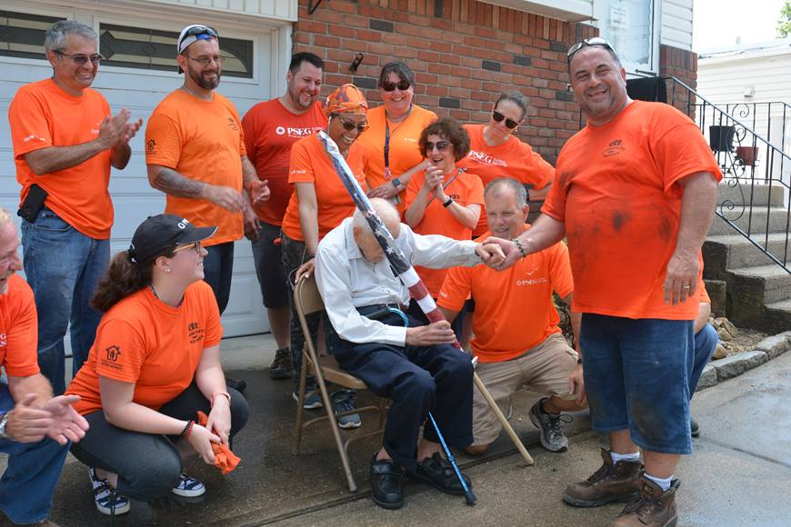 PSEG Long Island employee Nick Giorlando (foreground) presents WWII Army Air Force veteran Ralph Cavaliere with a new American flag for his home. Giorlando and a dozen of his coworkers recently spent a hot summer day cleaning up the 93-year-old's home and making it safer and more joyful for him to live there.