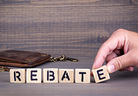 The word Rebate being spelled out with Scrabble letters on a table with a wallet in the background