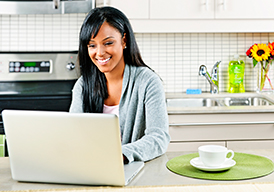 Smiling woman sitting in her kitchen with a cup of coffee working on a laptop