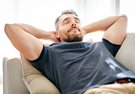 Man relaxing and leaning back with his eyes closed