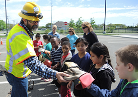 Technician showing safety equipment to a group of schoolchildren