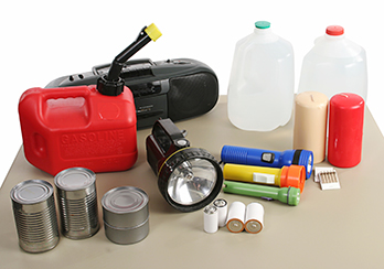 Emergency supplies (batteries, flashlight, radio, water, etc.) on a table