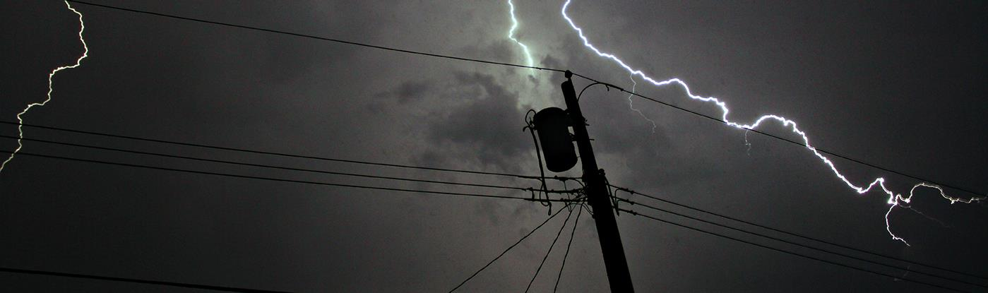 Lightning strike in sky behind a utility pole & wires