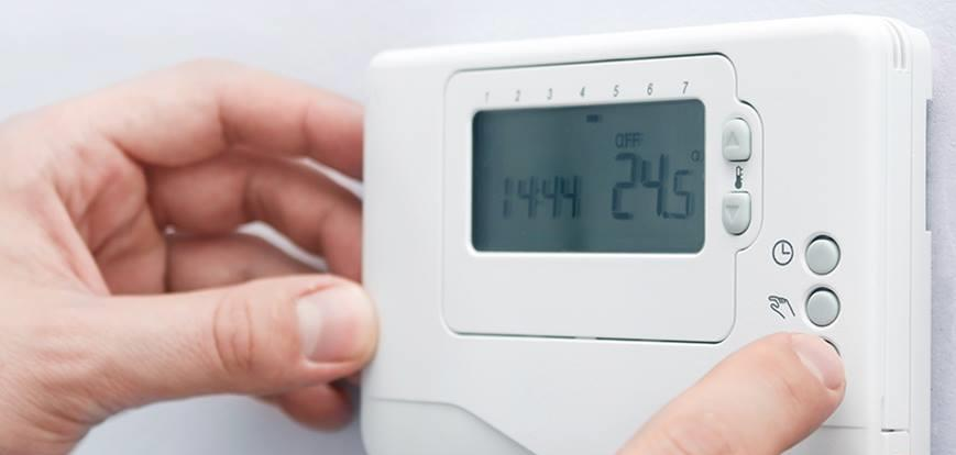 Fingers adjusting the settings on a digital thermostat