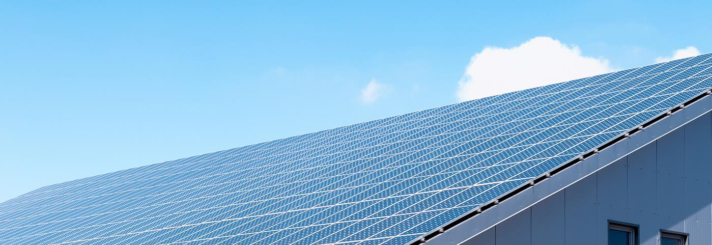 A roof completely covered with solar panels set against a bright blue sky