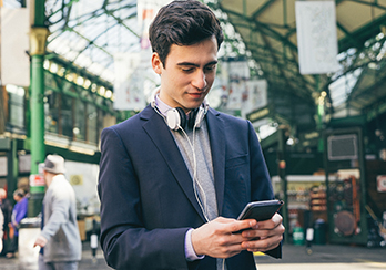 Young, male executive with headphones hanging around his neck, looking at his smartphone