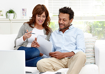 Couple sitting on a couch and reviewing bills