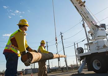 Two workers in hard hats guiding a utility pole that is being hoisted by a crane