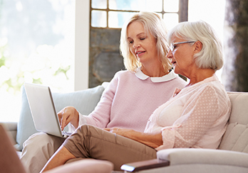 An older and a younger woman sitting together on the couch, looking at a computer