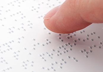 A finger hovering over a document written in Braille