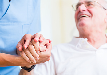 Older man sitting, holding hands with healthcare worker