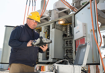 A PSEG Long Island technician examining diagnostics at an electricity substation