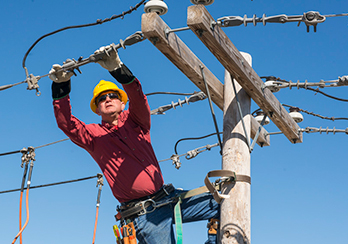 A utility worker connected to the side of a utility pole while repairing wires