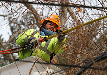 A utility worker in a bucket lift repairing wires