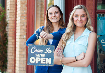 "Two women standing in front a store front, one woman is holding a sign that says ""Come In, We"