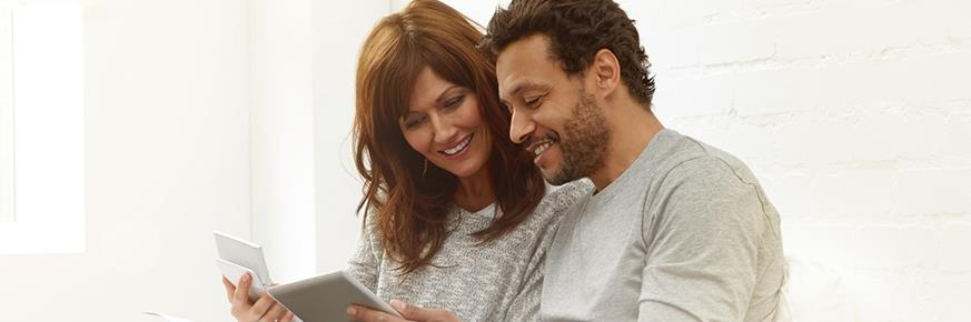 A couple looking at a tablet and a piece of paper
