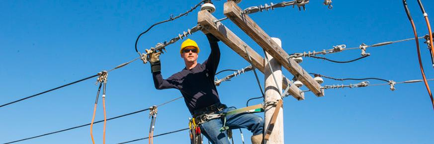 A technician working on a utility pole