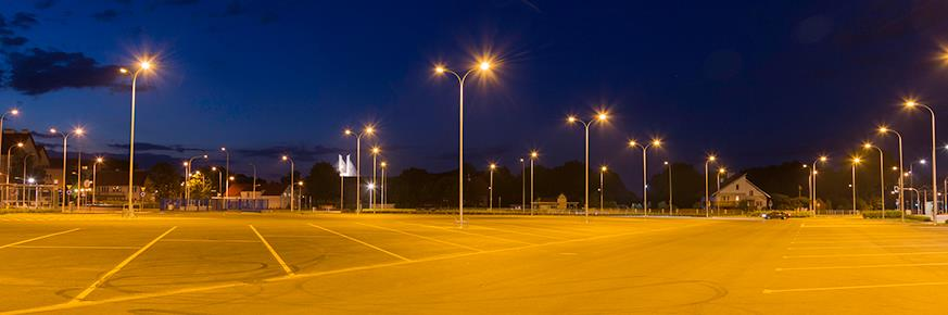 A large parking lot illuminated by streetlights