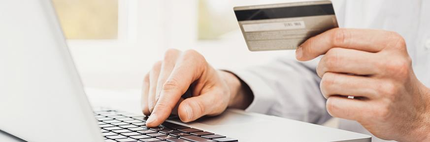 Closeup of man holding credit card and entering information into laptop